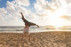 Gain emotional freedom from what pushes your buttons so you feel like this woman doing cartwheels on the beach